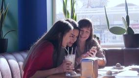 Amiche felici che fanno selfie sul telefono cellulare al caffè alla luce del sole stock footage