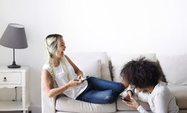 Amiche felici che per mezzo insieme dello smartphone a casa Immagini Stock