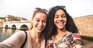 Amiche multiculturali che prendono selfie divertendosi insieme - concetto di amicizia con le ragazze felici alla vacanza della ci fotografia stock