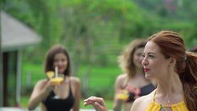 Amiche nello stagno Partito nelle vacanze estive Vetri del tintinnio delle ragazze con i cocktail alcolici archivi video