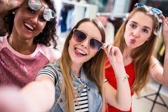 Amiche sorridenti che indossano gli occhiali da sole alla moda divertendosi tempo che prende selfie con il telefono cellulare men immagini stock