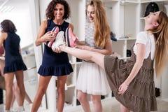 Amiche sorridenti divertenti divertendosi nel boutique che offre nuove calzature al loro amico che solleva la sua gamba per contr immagine stock libera da diritti