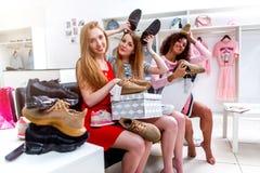 Amiche teenager positive divertendosi tempo insieme mentre facendo seduta di compera scegliendo le nuove scarpe che imbrogliano i immagine stock