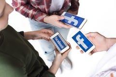 Amici adolescenti che per mezzo degli smartphones con il logo del facebook isolati su bianco Immagine Stock