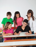 Amici adolescenti che per mezzo della compressa di Digital allo scrittorio Fotografia Stock