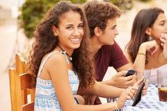 Amici adolescenti che si siedono al ½ del ¿ di Cafï facendo uso dei dispositivi di Digital Immagini Stock