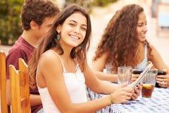 Amici adolescenti che si siedono al ½ del ¿ di Cafï facendo uso dei dispositivi di Digital Immagine Stock Libera da Diritti