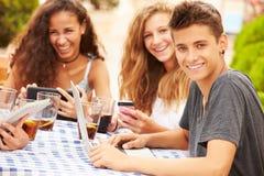 Amici adolescenti che si siedono al ½ del ¿ di Cafï facendo uso dei dispositivi di Digital Fotografia Stock Libera da Diritti
