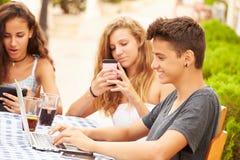 Amici adolescenti che si siedono al ½ del ¿ di Cafï facendo uso dei dispositivi di Digital Immagini Stock Libere da Diritti