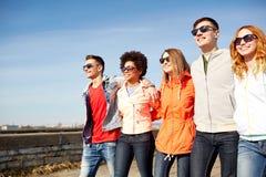 Amici adolescenti felici che camminano lungo la via della città fotografie stock