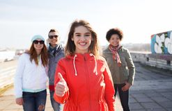 Amici adolescenti felici che mostrano i pollici su sulla via Fotografia Stock