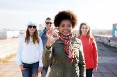 Amici adolescenti felici che mostrano segno giusto sulla via Immagine Stock Libera da Diritti