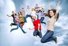 Amici adolescenti felici che saltano nel cielo Immagini Stock