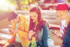 Amici adolescenti felici con gli smartphones all'aperto Fotografia Stock Libera da Diritti