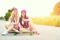 Amici adolescenti sorridenti dei pantaloni a vita bassa con il pattino, immagine colorised con sunflare Immagine Stock Libera da Diritti