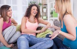 Amici affascinanti che bighellonano su un sofà in un salone Fotografia Stock