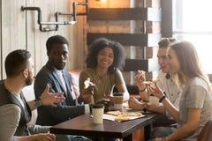 amici africani e caucasici Multi-etnici che parlano mangiando pizza Immagini Stock Libere da Diritti