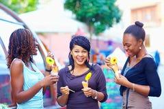 Amici africani felici che mangiano il gelato all'aperto immagini stock libere da diritti