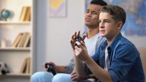 Amici afroamericani e caucasici insoddisfatti del video gioco perdente, dipendenza stock footage