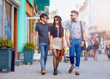 Amici alla moda che camminano la via della città Immagine Stock