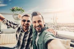 Amici allegri al caffè all'aperto che fa selfie Fotografie Stock