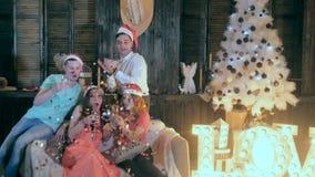 Amici allegri alla festa di Natale Scintille dei fuochi d'artificio, volo dei coriandoli nell'aria al partito stock footage