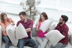 Amici allegri che giocano lotta di cuscino, sedentesi sullo strato Fotografie Stock Libere da Diritti