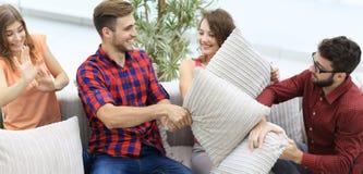 Amici allegri che giocano lotta di cuscino, sedentesi sullo strato Immagine Stock