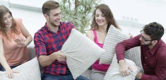 Amici allegri che giocano lotta di cuscino, sedentesi sullo strato Immagine Stock Libera da Diritti