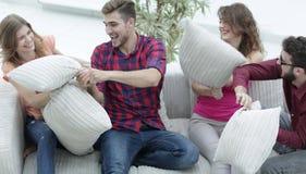 Amici allegri che giocano lotta di cuscino, sedentesi sullo strato Fotografia Stock