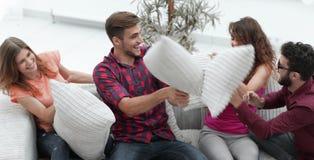 Amici allegri che giocano lotta di cuscino, sedentesi sullo strato Immagini Stock Libere da Diritti