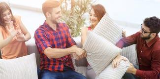 Amici allegri che giocano lotta di cuscino, sedentesi sullo strato Fotografie Stock