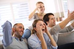 Amici allegri che guardano partita di football americano a casa immagini stock