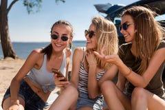 Amici allegri che riposano sulla spiaggia fotografia stock