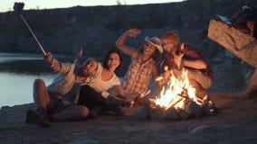 Amici allegri che si rilassano intorno al fuoco di accampamento archivi video