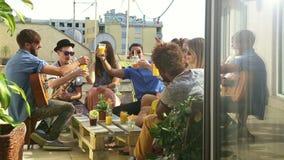 Amici allegri che tostano su un terrazzo del tetto video d archivio