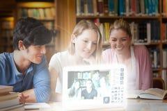 Amici allegri dell'istituto universitario che guardano le foto sull'interfaccia digitale Fotografie Stock