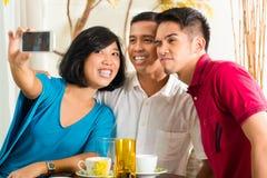Amici asiatici che catturano le maschere con il telefono cellulare Fotografia Stock
