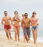 Amici attivi che corrono alla spiaggia sabbiosa Immagini Stock