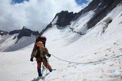 Amici belaying della ragazza dell'alpinista dalla corda Immagine Stock