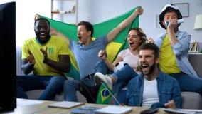 Amici brasiliani felici che guardano partita a casa celebrare scopo della squadra di football americano immagine stock