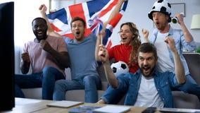 Amici britannici che guardano partita di football americano sulla TV, scopo d'esultanza della squadra nazionale fotografia stock