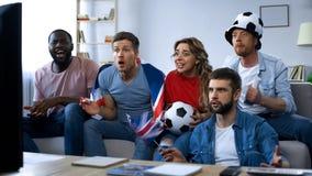 Amici britannici che sostengono squadra nazionale, partita di football americano di sorveglianza sulla TV a casa fotografie stock
