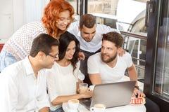Amici in caffè con il computer portatile Fotografie Stock Libere da Diritti