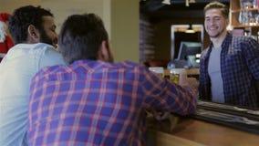 Amici che bevono birra al contatore in pub stock footage