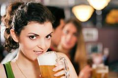 Amici che bevono birra in barra Fotografia Stock Libera da Diritti