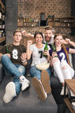 Amici che bevono birra e che mangiano popcorn Fotografie Stock Libere da Diritti