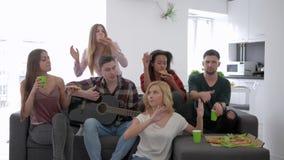 Amici che cantano con la chitarra e che mangiano pizza che si siede sul partito, sull'amicizia e sulla relazione del sofà a casa