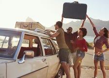 Amici che caricano bagagli sullo scaffale di tetto dell'automobile pronto per il viaggio stradale fotografia stock