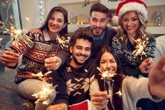 Amici che celebrano il Natale con le stelle filante Fotografie Stock Libere da Diritti